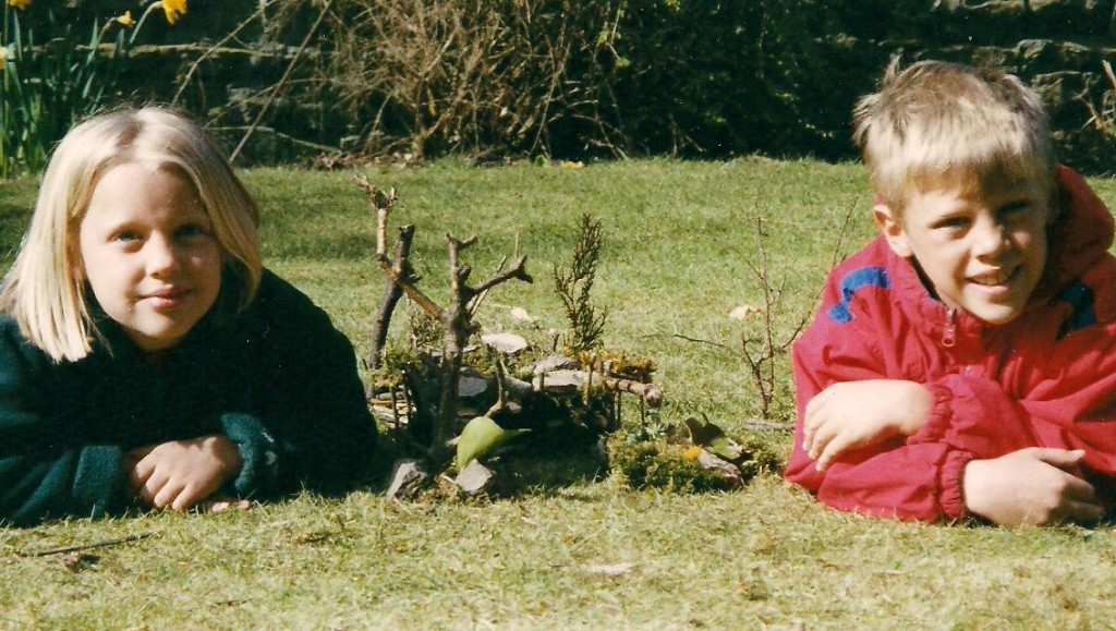 Inga and Erik with their house of twigs and stones, English Lake District.