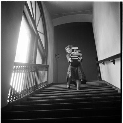 columbia-university-woman-carrying-a-large-stack-of-books by stanley kubrick